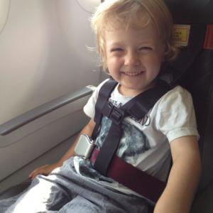 Mit Cares-Gurt im Flugzeug gesichertes Kleinkind
