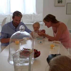 Fotoshooting für einen Hersteller von Babynahrung mit einem Kindermodel und zwei erwachsenen Models.