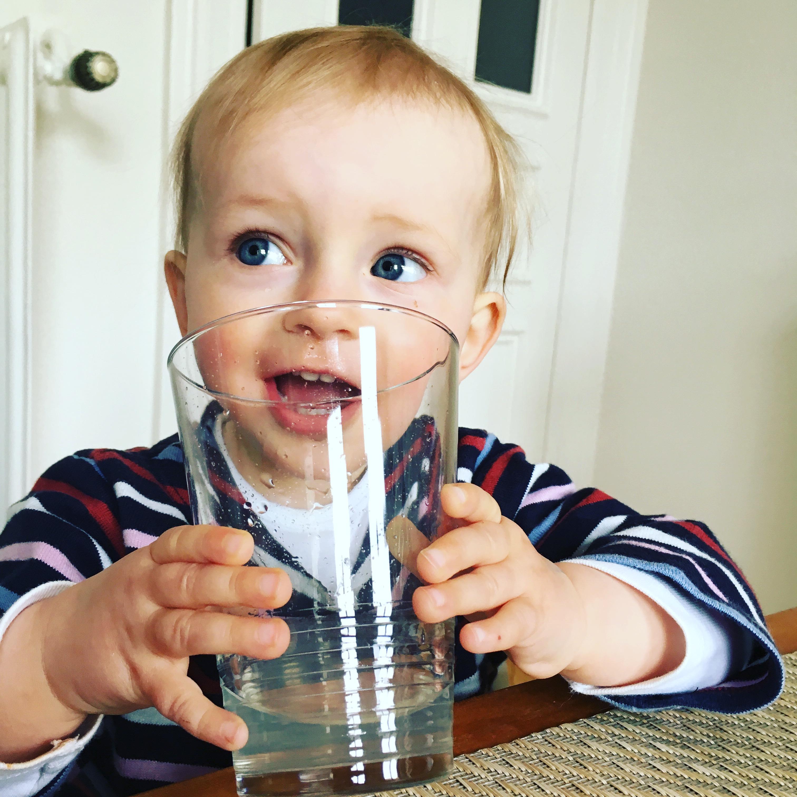 Kleinkind trinkt aus Glas