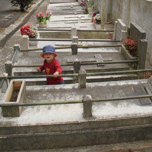 Kleines Kind zwischen Gräbern auf einem Friedhof