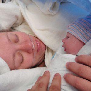 Neugeborenes in den Armen der Mutter im Kreißsaal