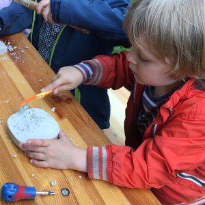 Kind gräbt ein Dinosaurier-Skelett aus einem Gipsblock aus