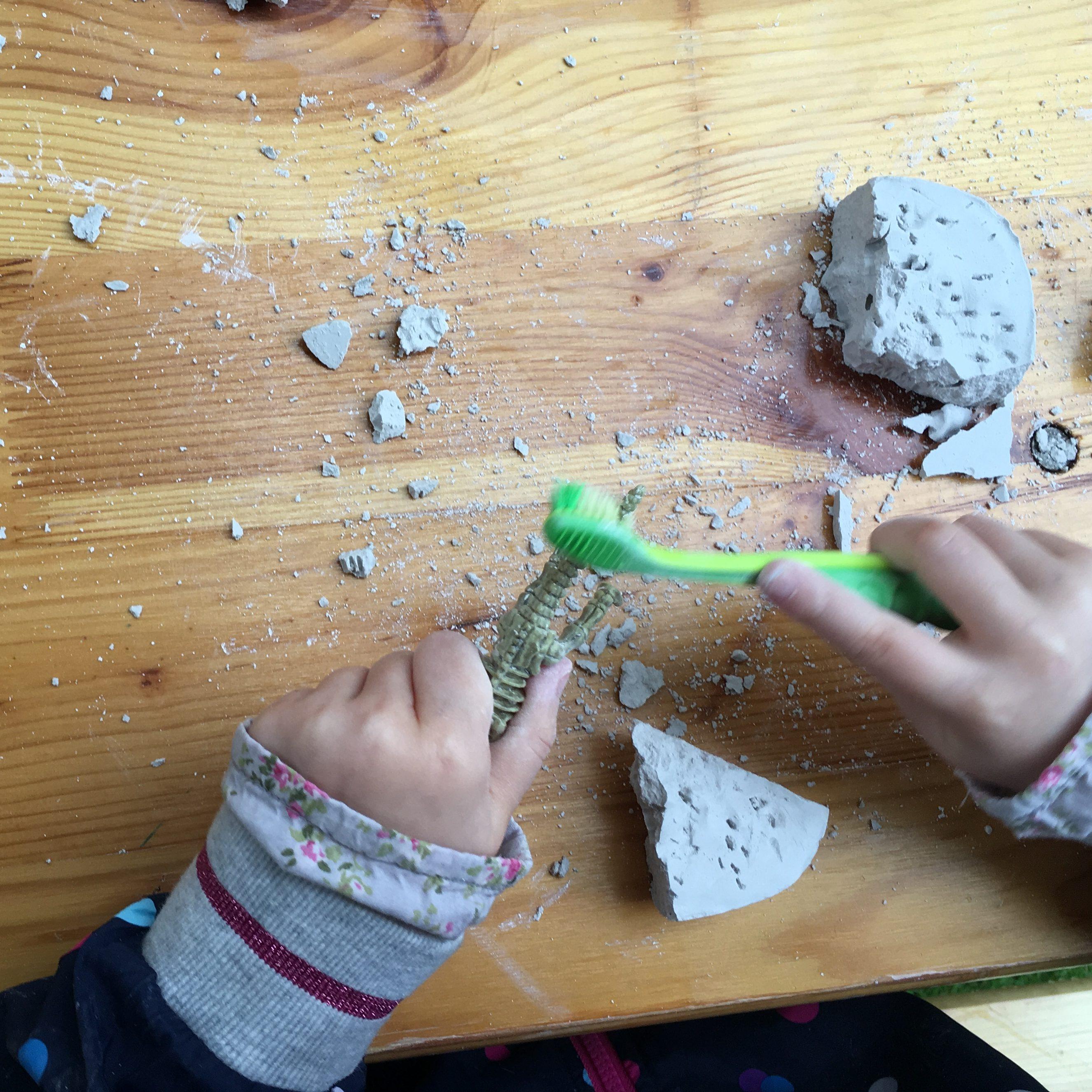 Kind gräbt Dinosaurier aus Gipsblock aus